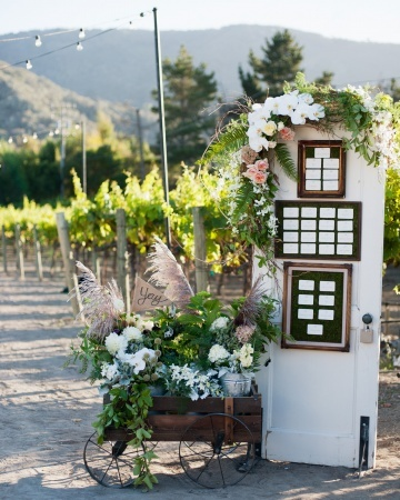 "An ""entryway"" made from an old door is propped perfectly in position to hold escort cards"
