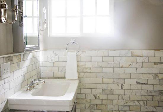 calcutta marble, grey walls, circa light fixtures, natural light bathroom
