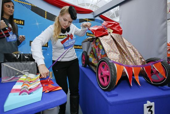 Julia Rose, a gift wrapper from North Richland, Texas shows off her technique by wrapping a go-kart in round two of the contest using Scotch Expressions Tapes.