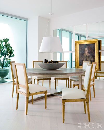 Chairs from And Beige surround a midcentury table, the portrait is 19th-century Russian, and the walls and ceiling are painted in  Bonifant White for Benjamin Moore.