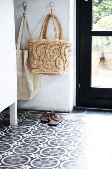 I love this floor, the black door, the bags on hooks.