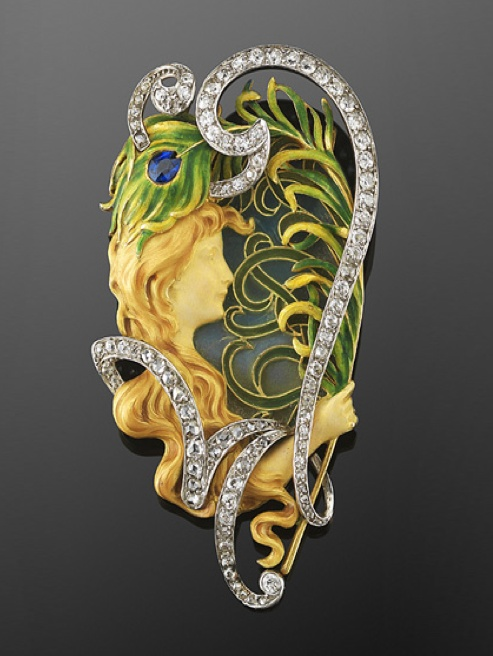 Art Nouveau Diamond and Enamel Maiden and Peacock Feather Brooch by Louis Aucoc  A diamond-set scroll with a total of approximately 2.20 carats frames an enameled maiden holding a peacock feather against a plique a jour enamel background, set in 18 karat yellow gold and platinum.