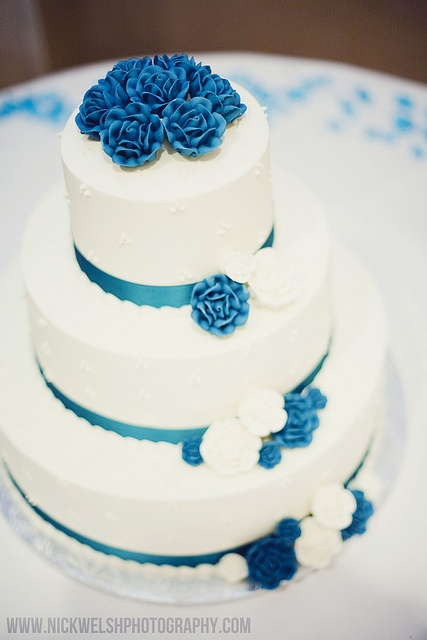 White wedding cake with blue accents.  www.nickwelshphot...