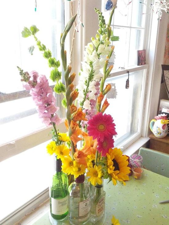 Bottles as vases + flower arrangement