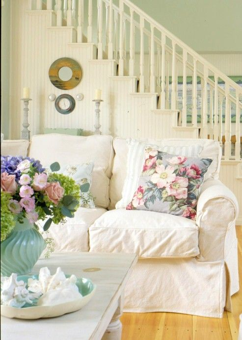 Love the cream hued wooden staircase, floral throw pillow, and vase of assorted, cheerful blooms. #room #shabby_chic #decor #home #house #vintage #vintage_chic #flowers #vase #couch #slip_cover #stairs #living_room