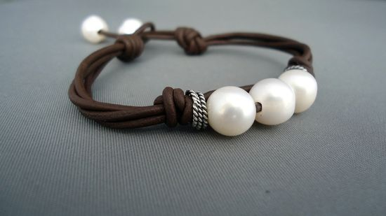 A perfectly knotted multiple strands of dark brown leather are strung onto these oxidize sterling silver rustic rings and 3 beautiful 10mm cultured pearls. Two pearls are gracefully place as a clasp with a leather knot at the end The bracelet measures between 7- 1/2 adjustable inches.  If you want a different length please let me know upon check out.