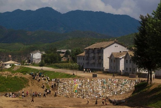 North Koreans work to build a sandbag wall on Monday, Aug 13, 2012 as they try to repair damage brought by July flooding in Songchon County, North Korea. Floods killed at least 169 North Koreans nationwide and destroyed tens of thousands of homes. Photo: David Guttenfelder / AP