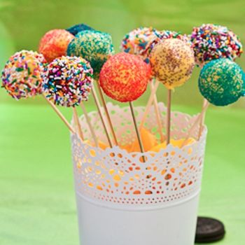 No Bake Oreo Cake Pops with light orange icing and various sprinkles.