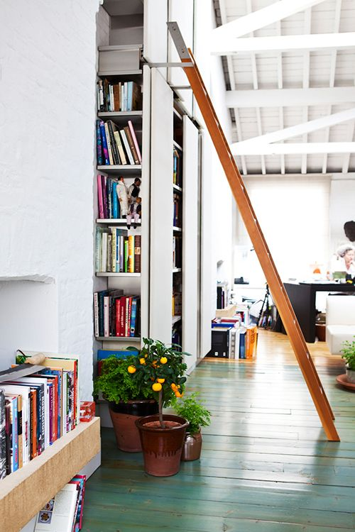 loft kitchen with built-in cookbook shelving & ladder