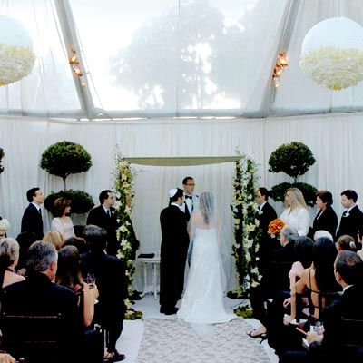 Topiaries and orchid-bedecked lanterns dressed up a tent at L'Orangerie restaurant in L.A. where the nuptials took place.