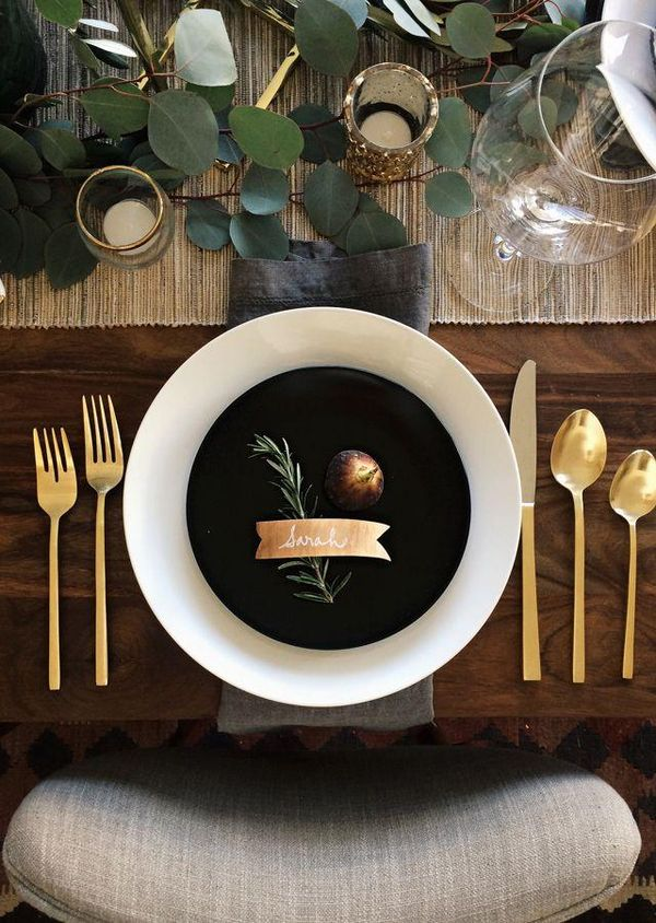 Such a gorgeous simple holiday tablescape: gold flatware, white china, a neutral table runner, dark gray linen napkin, with silver dollar eucalyptus and votives as the centerpiece. Classic and modern at the same time. This will seriously impress your guests!