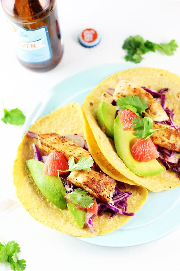 These Grapefruit & Avocado Fish Tacos are a delicious, healthy option for #TacoTuesday. Baked (not fried), and served with fresh grapefruit, creamy avocado, and a tangy cabbage slaw.   platingsandpairings.com