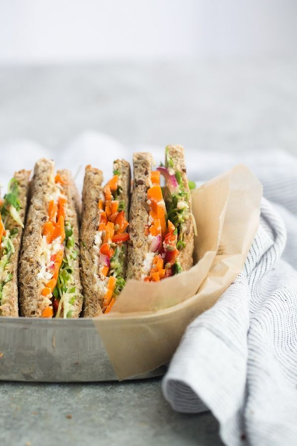A hummus sandwich packed with pickled carrots, feta, and sprouts that is perfect to pack for school, work, or a road trip.