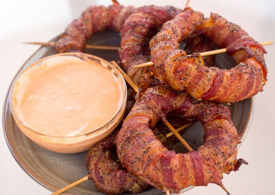 Bacon Wrapped Onion Rings w/ Sriracha Mayo Dipping Sauce. • 1 pack Bacon • 4-5 Sweet Onions • 2 T Black Pepper • 1/2 cup Sriracha Hot Sauce • 2 T Mayo • 1 tsp Lime Juice 1. Cut onions into 1 inch thick and have a sturdy ring. 2. Brush onion with hot sauce. 3. Wrap each ring with bacon and secure toothpick. 4. cover the onion rings with smoke, bake for 90 minutes at 250-350 degrees. spicy sriracha mayo, combine 2 T of mayo, 1 T of sriracha sauce, and 1 tsp of lime juice. Mix well.