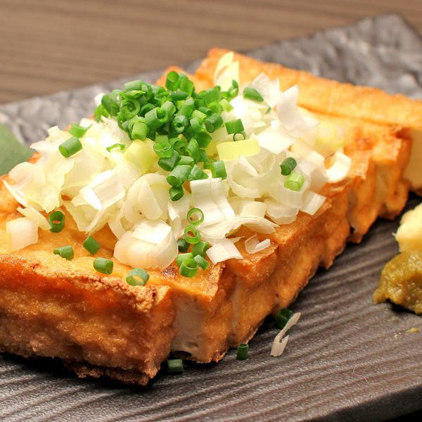 """Atsuage (Deep-fried Tofu block) Often used in WASHOKU and """"Atsuage no Shoga Joyu"""" is one of them. Toasted until it becomes crispy outside, served with grated ginger and soy sauce. Some extra toppings such as chopped green onions, bonito flakes can make this dish even more beautiful! Super simple, but you can enjoy the beautiful combination of crispiness and the smoothness of Tofu!"""