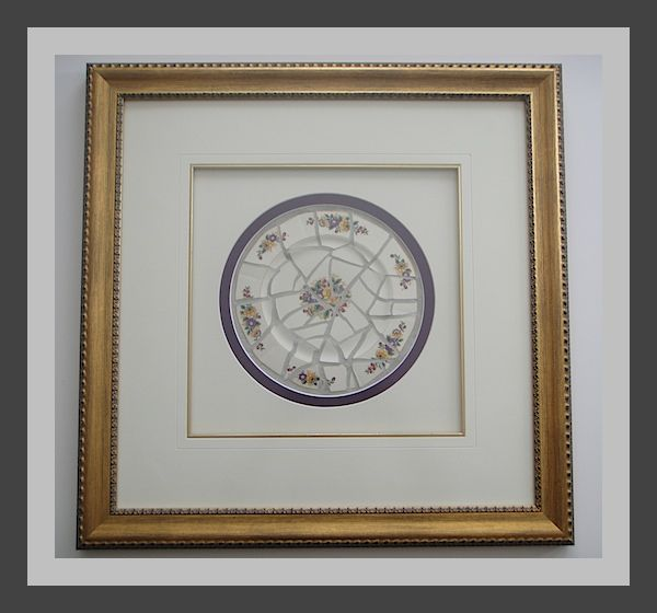 A broken plate.  Have a cracked or chipped antique plate? Don't know what to do with it?  Don't throw it away. Break it into several medium sized pieces, grout it like tile and have it framed.