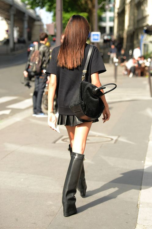 "All-black. Structured pieces. Strong leather boots and skirt add contrast to the loose T-shirt. Love the proportions. The top is long, with the short pleated skirt peeking under the hem. The boots are streamlined, and, like the hiked-up hemline of the skirt, it adds to the ""long legs"" effect."