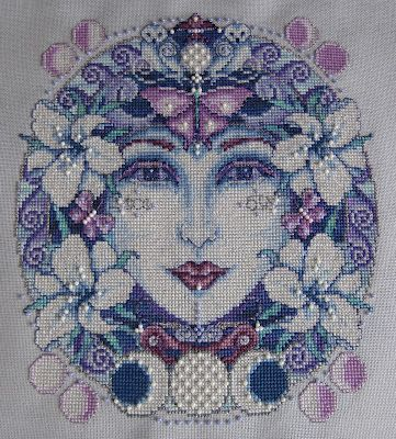 The pattern is called 'Mother Moon' and is available in a book called 'Bewitching Cross Stitch' by Joan Elliott.