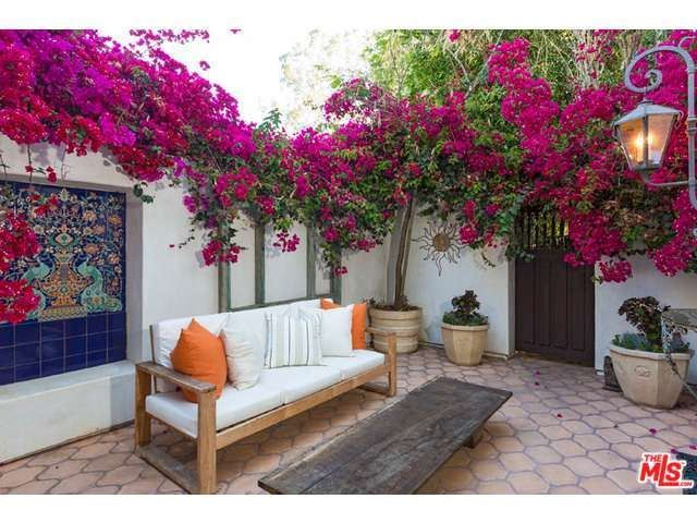 A soothing and colorful outdoor seating area. The bright flowers and custom art work tiling make this space inviting and dramatic. Pacific Palisades, CA Coldwell Banker Residential Brokerage $11,380,000