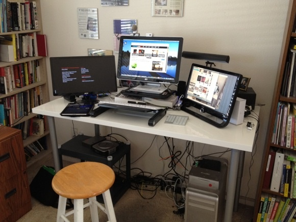 Standing Desk    Put together an affordable standing desk with materials from Ikea– Vika Amon Table top and four Vika Kaj Legs.     Any suggestions for hiding and better organizing the wires below?