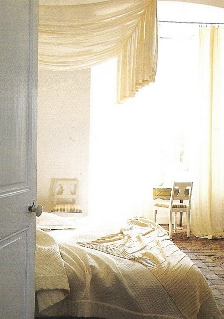 Soft and bright bedroom with white linens and a brick floor.