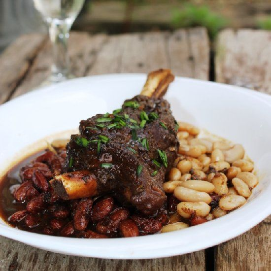 Lamb shank braised until fork tender with baked navy bean and red bean ...