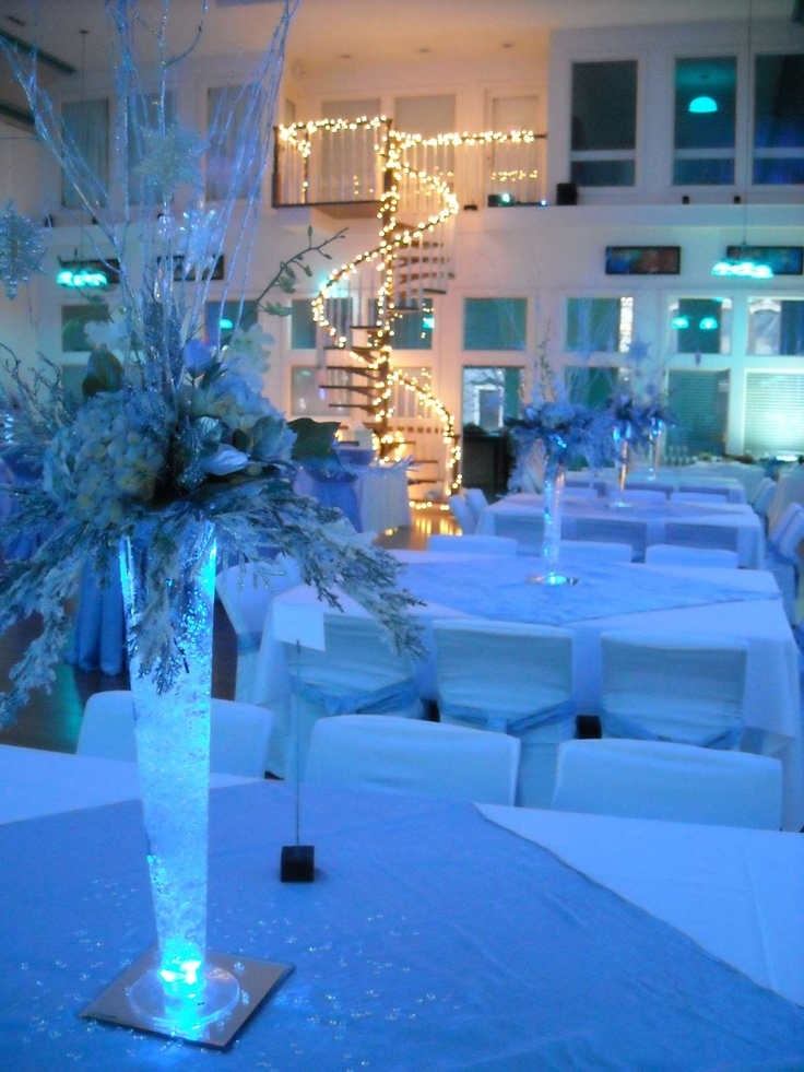 "The bride & groom wanted an ""icy"" feel, so they used cool white and blue linens, with dramatically lighted centerpieces.  The spiral staircase was the only ""warm"" lighting in the room, making quite an impact!"
