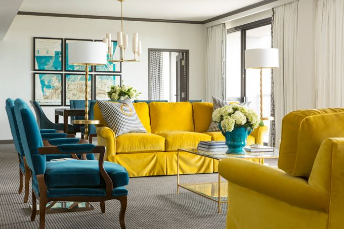 The Chancellor Suite at The Chancellor Hotel. Yellow & blue living room with pair of canary yellow velvet rolled-arm sofas, peacock blue teal velvet French chairs, brass floor lamps, turquoise blue urn vase and gray moldings.