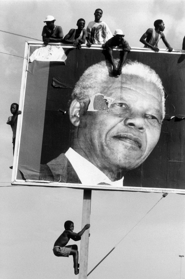 © Ian Berry - Supporters climb to every vantage point whilst awaiting the arrival of Nelson Mandela in a Natal township. South Africa, 1994. °
