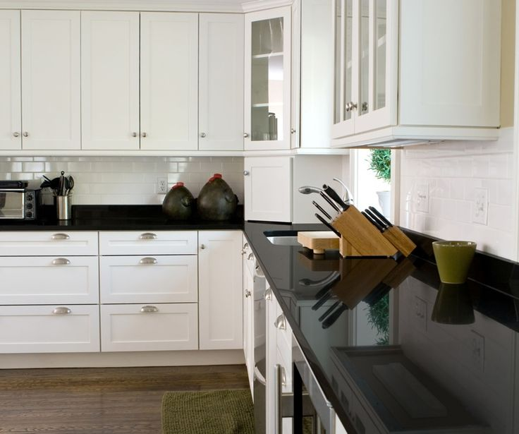 kitchen cabinets with cup pulls, glass uppers, dark wood floors, dark
