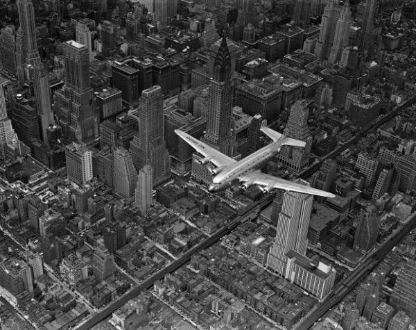 An aerial view of a DC-4 passenger plane flying over midtown Manhattan in 1939