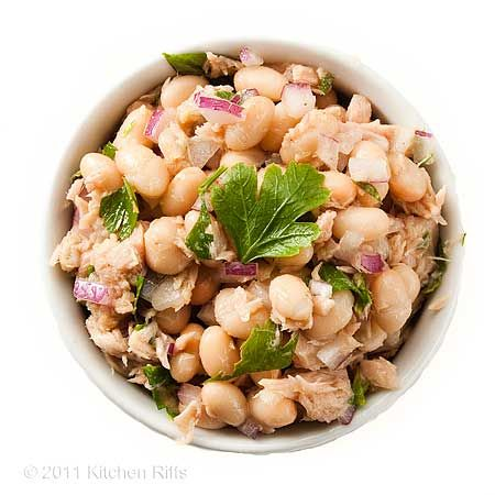 White Bean and Tuna Salad in ramekin on white background, overhead ...