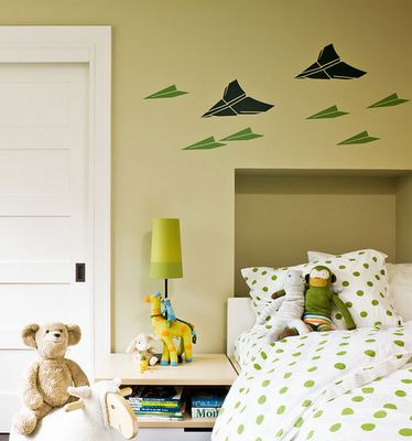 The fun airplane wall mural is painted in kelly and hunter greens.