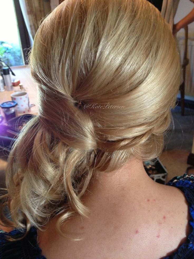 Curled and pinned to the side.