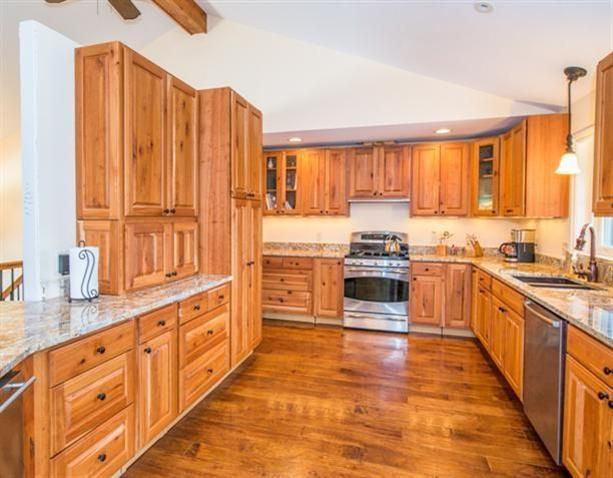 The Kitchen Features Natural Cherry Cabinets Granite Countertops