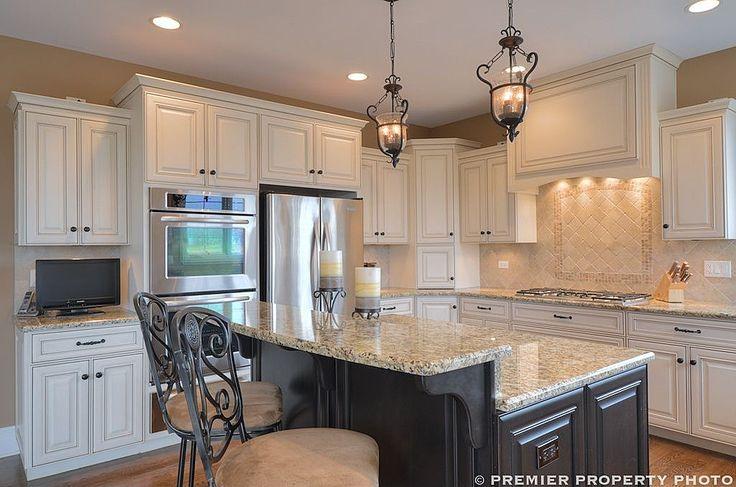 Glazed white cabinets, dark island, travertine backsplash, lantern