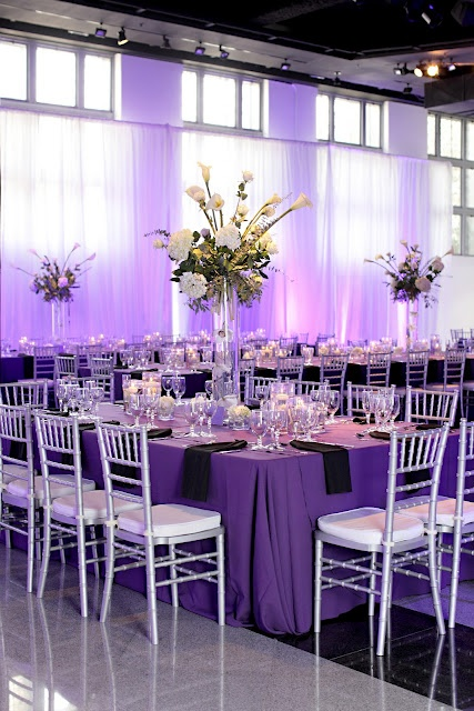 White And Green Centerpieces Of Hydrangea And Calla Lily On Purple Linens With Black Napkins