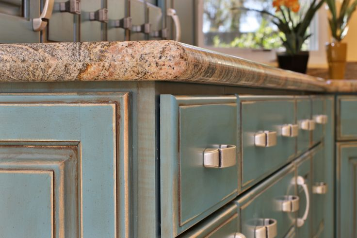 Turquoise cabinetry with a rust glaze and granite countertops help