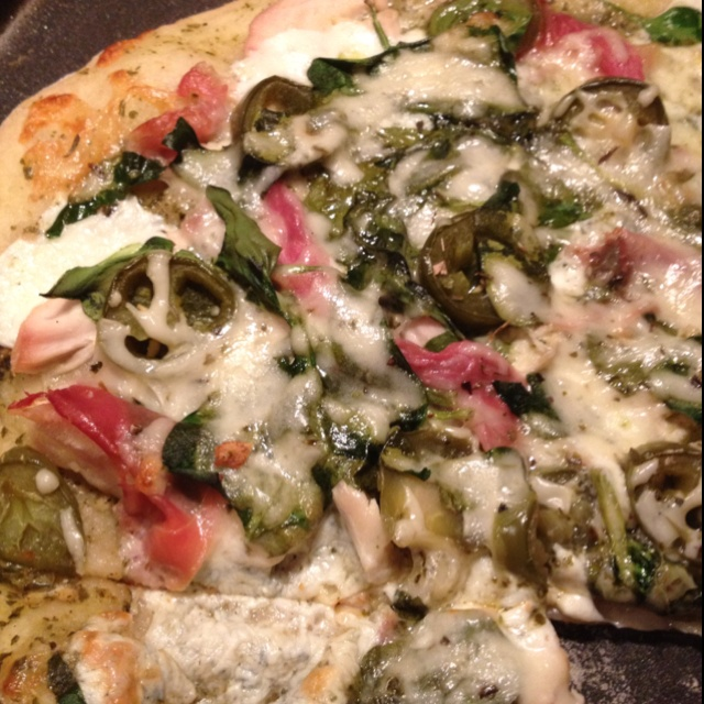 White pizza with spinach, basil, tomatoes, prosciutto, jalapeño, and ...