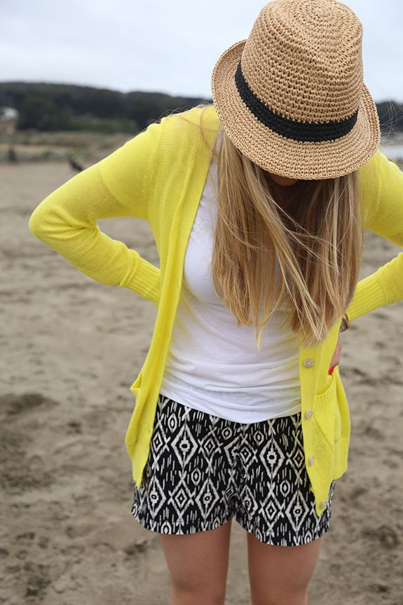 Black and white printed shorts, white vintage tee, neon textured cardigan, straw fedora in stores.
