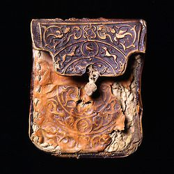 The wallet has a decoration that was made by stamping the leather in a matrix, after which the background around the stamped pattern was dyed dark brown. The pattern consists of arabesques populated by running four-legged animals and birds – a decoration that was also used in metalwork from Khorasan and Afghanistan from about 1200. On the back of the wallet are remnants of the leather straps that made it possible to attach the wallet to its owner's belt.