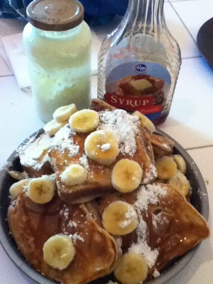 Fluffy French Toast topped with powdered sugar and bananas with ...