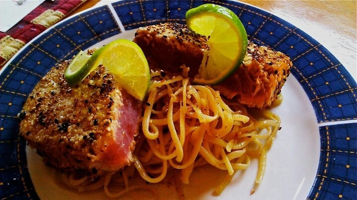 Sesame crusted tuna steak, resting on a bed of spicy Asian noodles