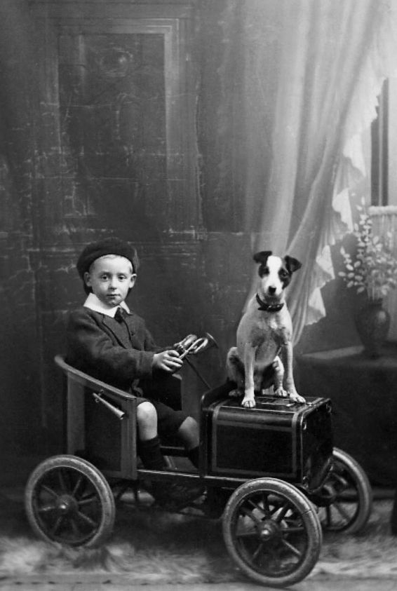 portrait of a boy and his dog sitting in a toy car. 1912