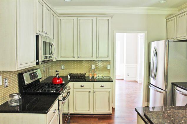 resurfaced builder's grade cabinets, mosaic glass backsplash, new lighting and appliances. Kitchen by Erika Ward Interiors