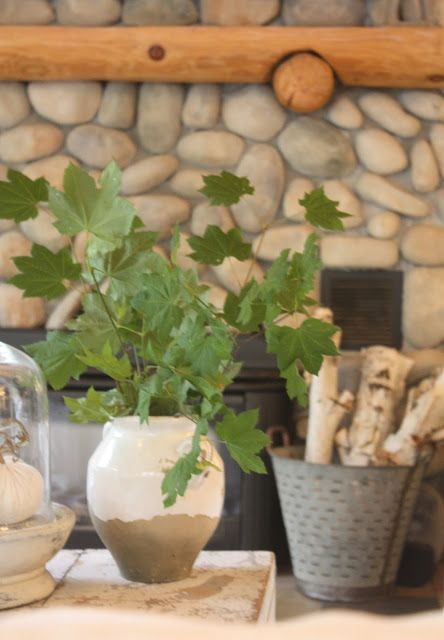 Love the olive bucket full of birch logs against the stone fireplace!