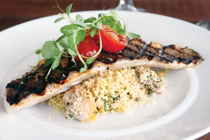 Grilled branzino over couscous and clams in a roasted lemon ...
