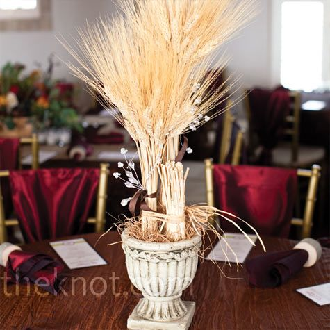 Wheat in a skinny vase with colored rocks and a ribbon tied around the vase for the center pieces
