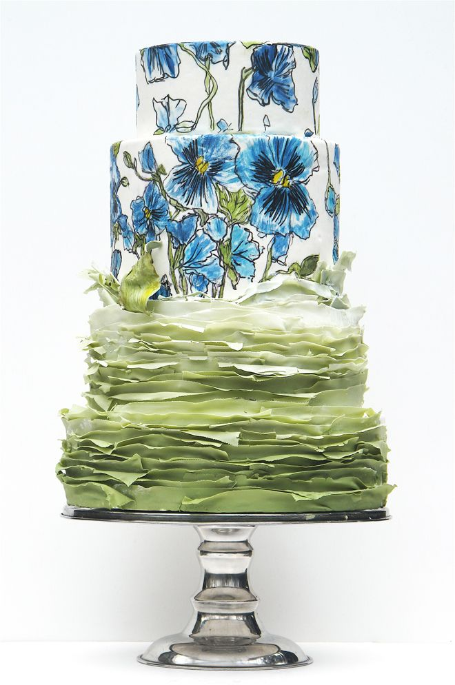 Gorgeous wedding cake featuring two blue and white floral print (pansies) layers and ruffled bottom layer in medium sage green.