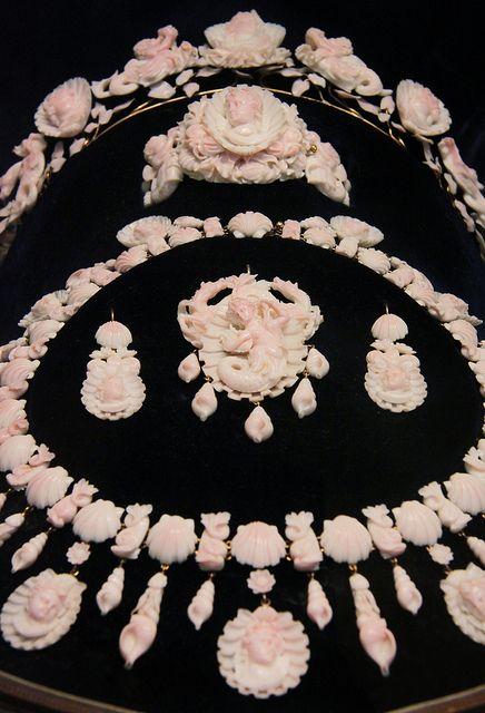 """Coral камео комплект украшений, 1850-70, Неаполь, Italy.A полной Parure сделаны из редкого розового коралла, известного как """"ангел skincoral"""" из-за его полупрозрачного appearance.It вырезана с морскими коньками, русалки, дельфины и снарядов, придает золотых рамках."""